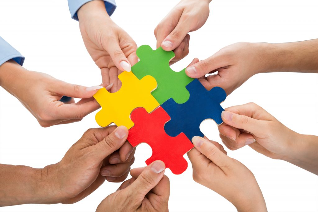 Close-up Of People Hands Connecting Together Jigsaw Pieces